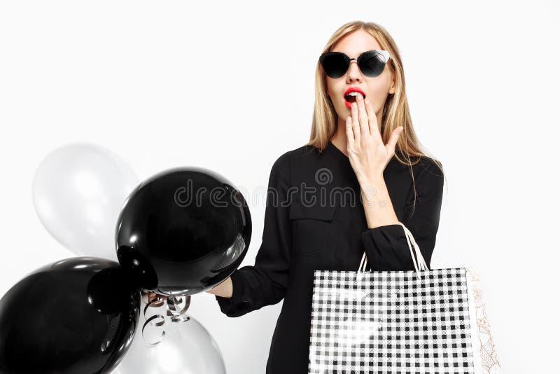 Menina chocada elegante, no vestido preto com óculos de sol, com sacos fotografia de stock royalty free