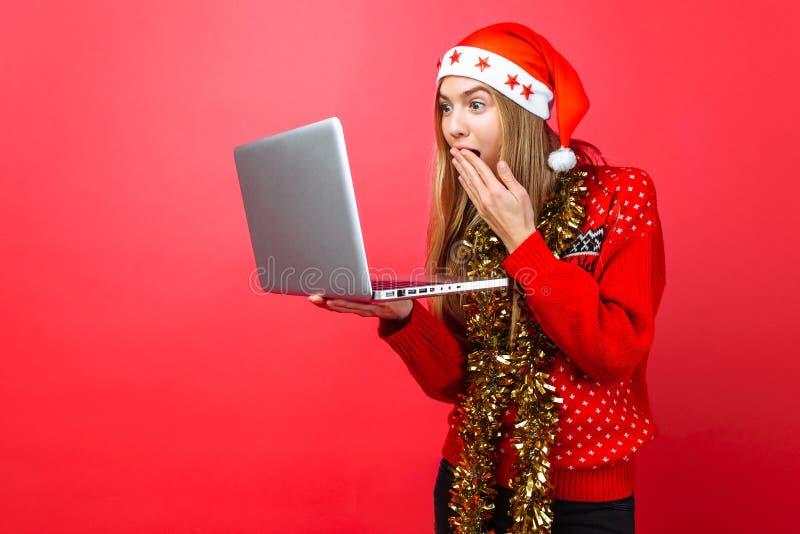 A menina chocada em uma camiseta e em um chapéu vermelhos de Santa Claus, com um portátil à disposição, olha na surpresa na tela  fotos de stock