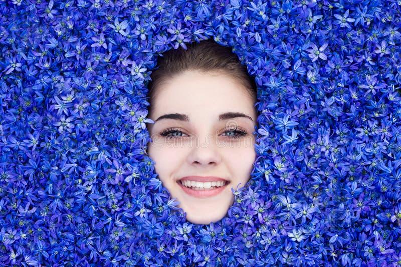 A menina ? coberta com as flores azuis da mola, a menina olha para fora de debaixo das flores fotografia de stock