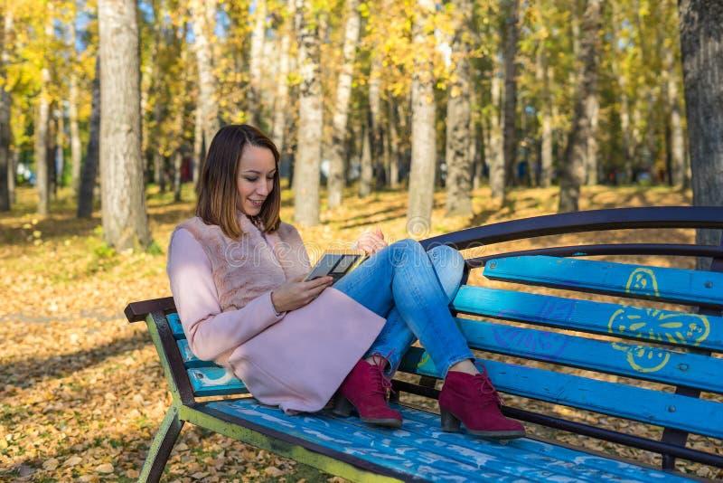 A menina coloca em um banco no parque do outono fotografia de stock
