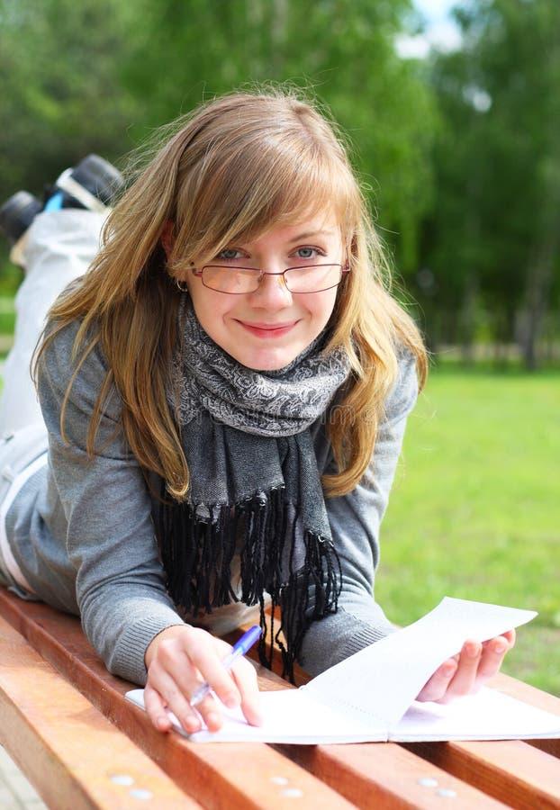 A menina colocada em um banco, e escreve imagens de stock
