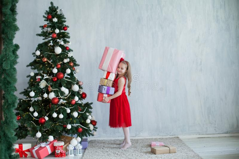 Menina com a árvore de Natal do ano novo dos presentes em presentes cinzentos de um fundo imagem de stock