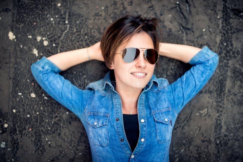 Menina com óculos de sol que ri e que sorri, pendurando para fora no telhado da construção Conceito ativo novo dos povos do estil imagem de stock royalty free