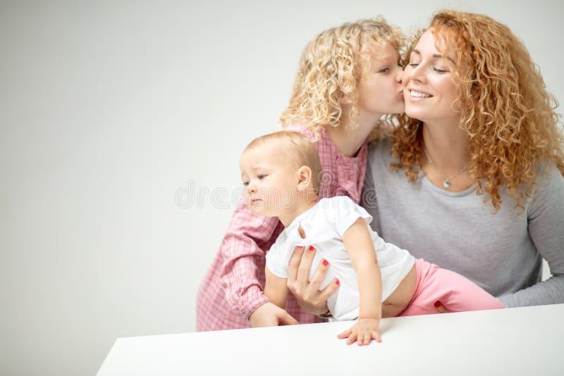 Menina com amores encaracolados da lebre do lonf suas mãe e irmã mais nova foto de stock