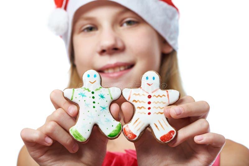 Menina com as cookies do homem de pão-de-espécie do Natal nas mãos fotografia de stock