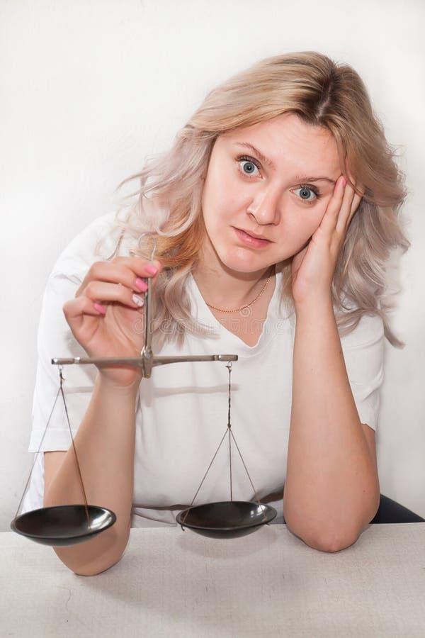 A menina com as escalas em suas mãos em um fundo claro toma uma decisão, pesa os argumentos imagem de stock royalty free