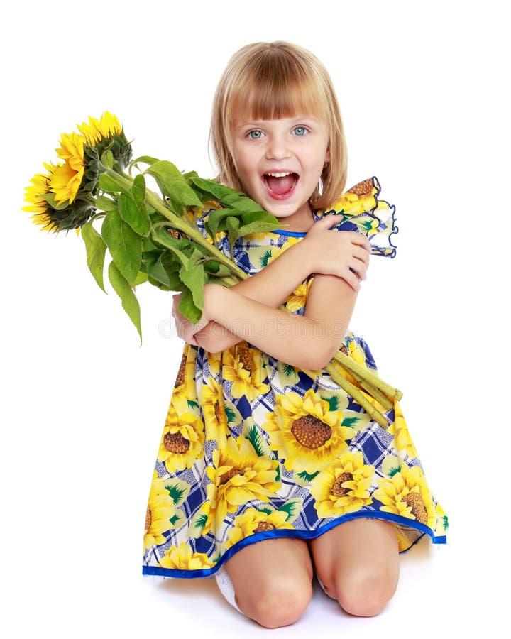 Menina com as flores do girassol imagem de stock
