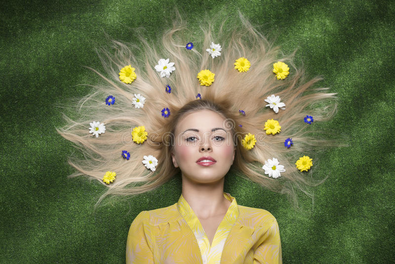Menina com as flores no cabelo foto de stock royalty free