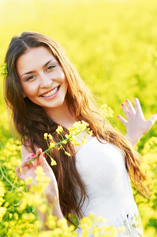 Menina com as flores no campo do verão imagens de stock royalty free