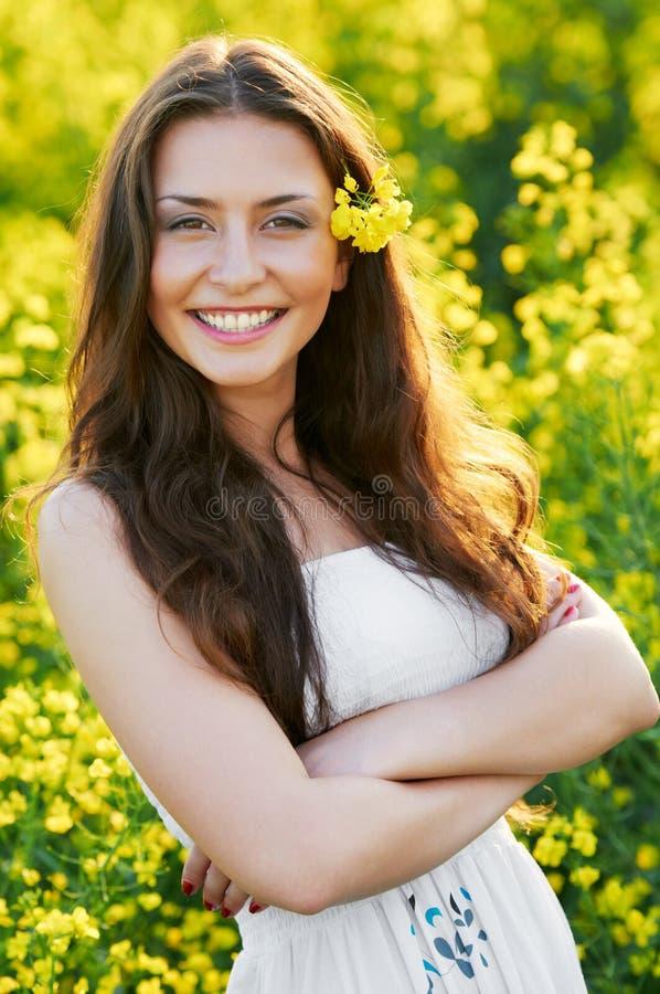 Menina com as flores no campo do verão imagem de stock