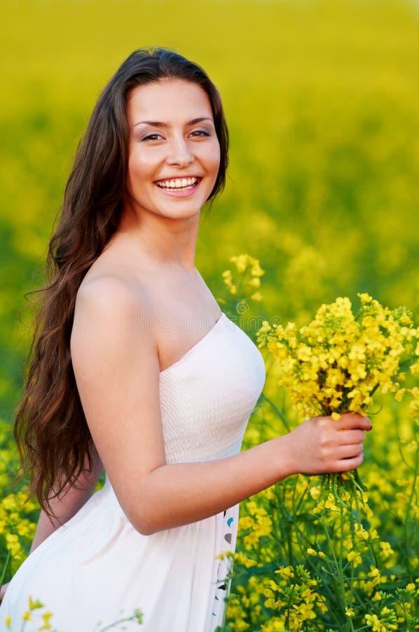Menina com as flores no campo do verão imagens de stock