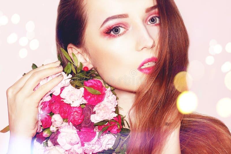 Menina com as flores no estúdio, modelo com cabelo moreno longo Mulher com o ramalhete de flores cor-de-rosa Modelo de forma Girl fotografia de stock