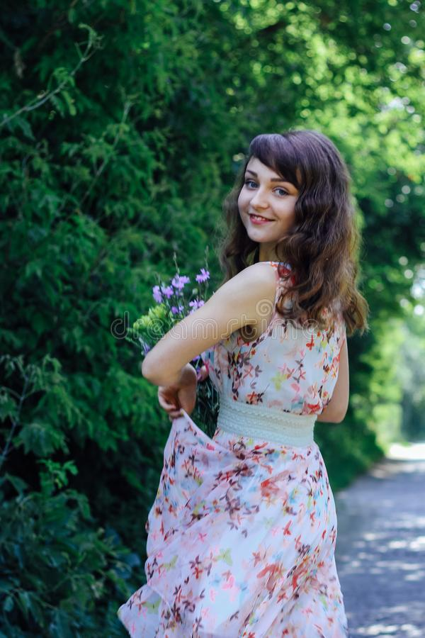 Menina com as flores selvagens em suas mãos imagens de stock