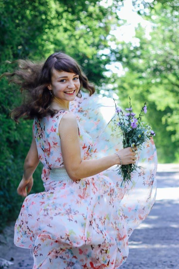 Menina com as flores selvagens em suas mãos fotografia de stock