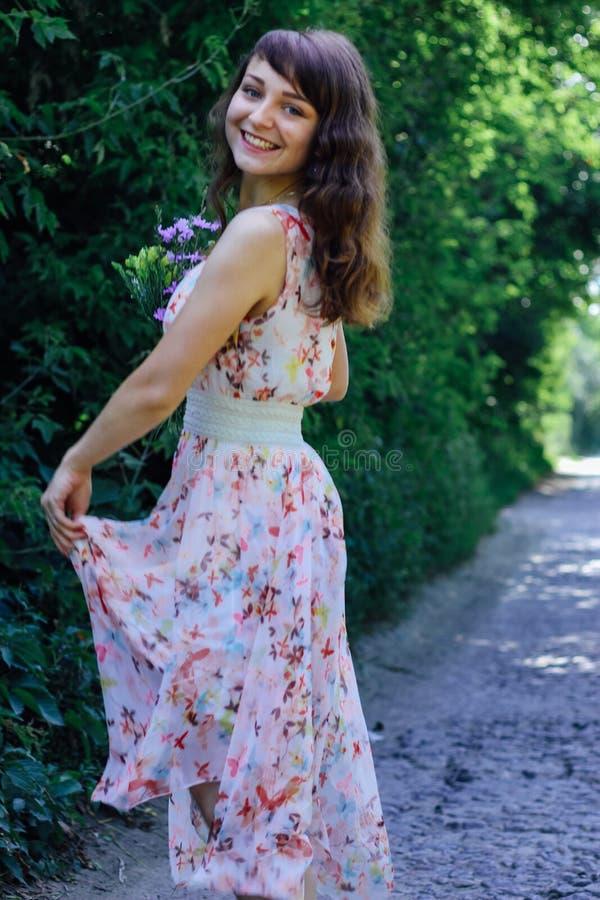 Menina com as flores selvagens em suas mãos imagem de stock royalty free