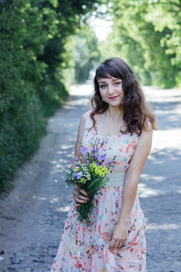 Menina com as flores selvagens em suas mãos imagens de stock royalty free