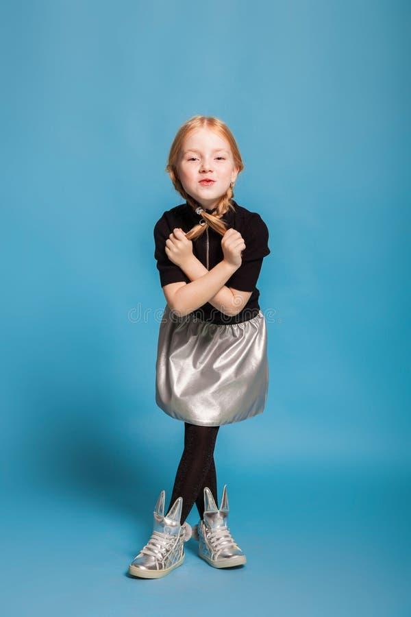 Menina com as tranças na roupa à moda no fundo azul fotografia de stock