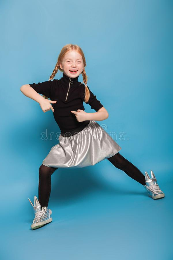Menina com as tranças na roupa à moda no fundo azul imagens de stock