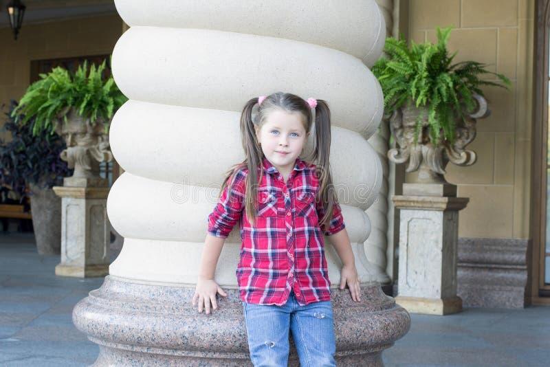 Menina com as tranças nas calças de brim fotos de stock royalty free