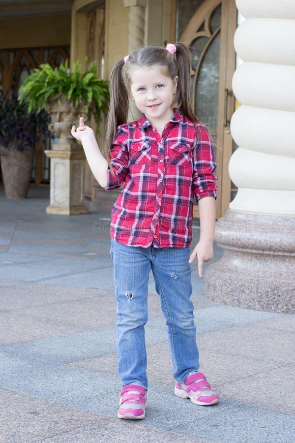 Menina com as tranças nas calças de brim fotografia de stock