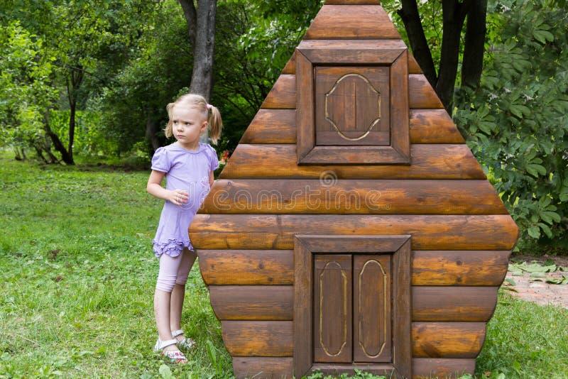 Menina com as tranças que jogam na cabana rústica de madeira do brinquedo fotos de stock royalty free