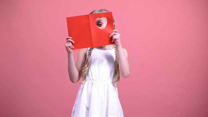 Menina com as tranças que olham através do furo coração-dado forma no cartão do Valentim imagem de stock royalty free