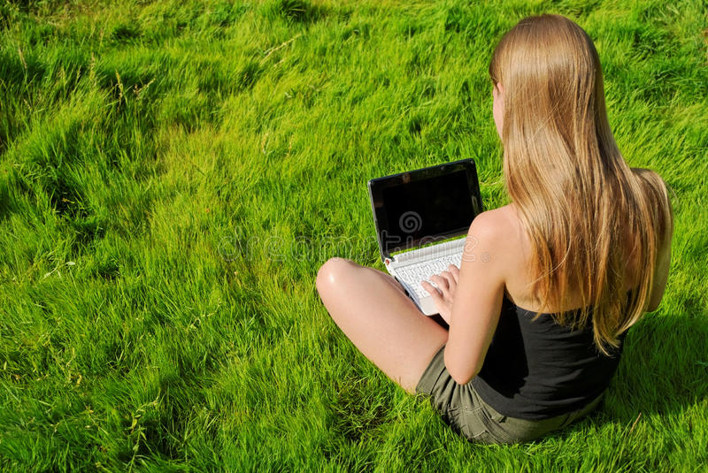 Menina com assento do portátil fotografia de stock