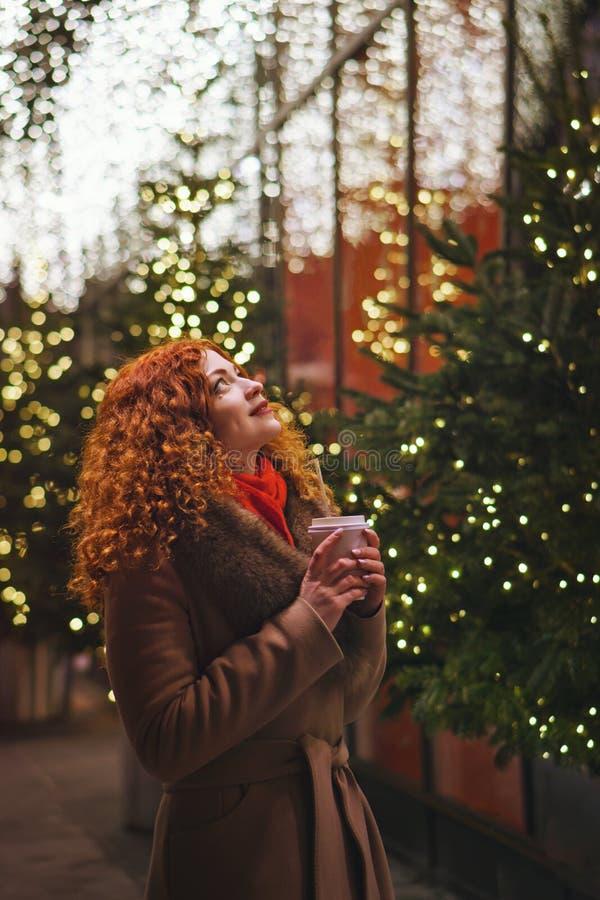 Menina com bebida de aquecimento Luzes festivas fotos de stock