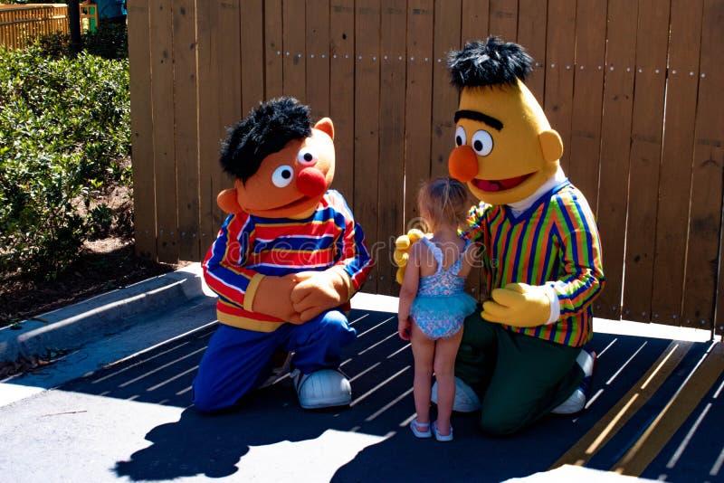 Menina com Bert e Ernie na área do Sesame Street em Seaworld na ?rea internacional 3 da movimenta??o imagens de stock