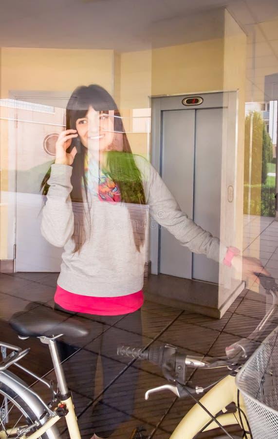 Menina com a bicicleta do fixie que sae do salão atrás de um vidro imagens de stock
