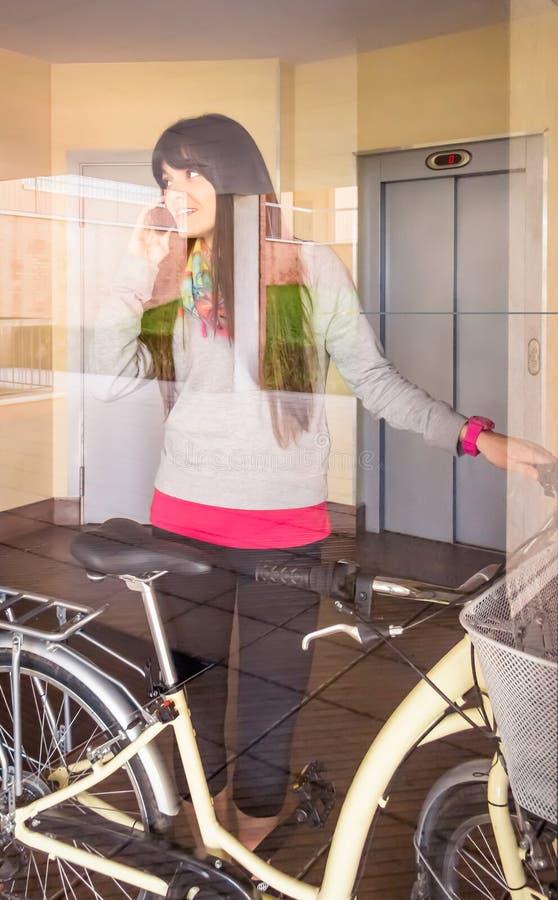 Menina com a bicicleta do fixie que sae do salão atrás de um vidro fotografia de stock