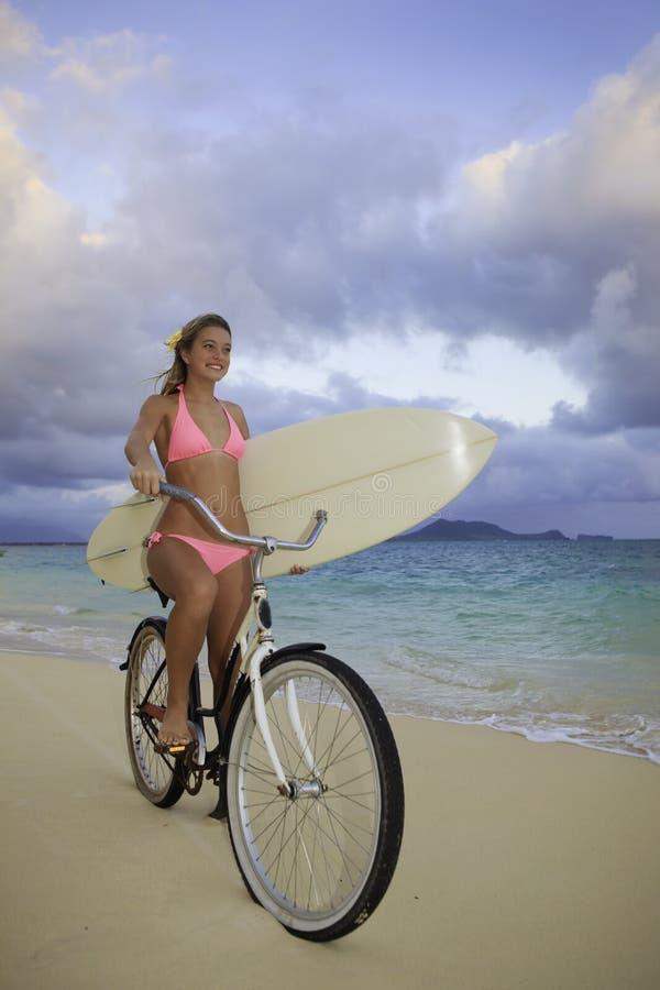Menina com bicicleta e prancha fotografia de stock