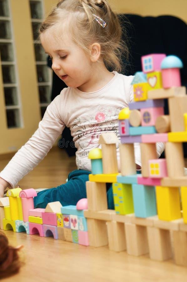 Menina com blocos de madeira do brinquedo imagens de stock