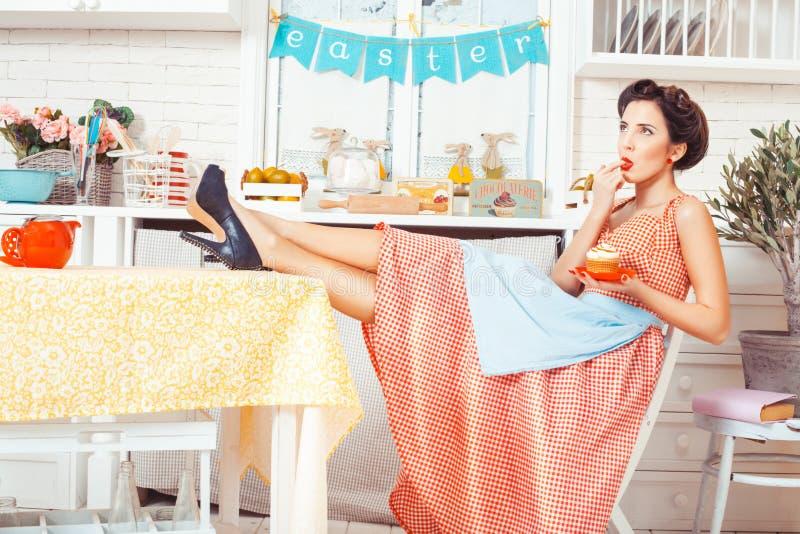 Menina com a boca do dedo na cozinha fotografia de stock royalty free