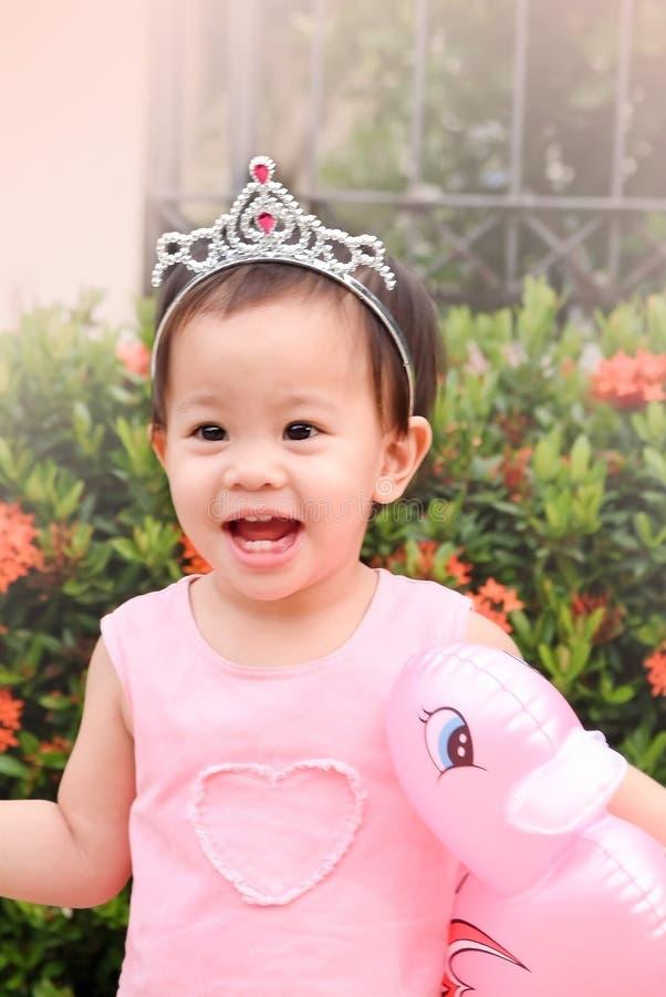 Menina com a boneca cor-de-rosa do pato à disposição e vestido e diade cor-de-rosa imagem de stock royalty free