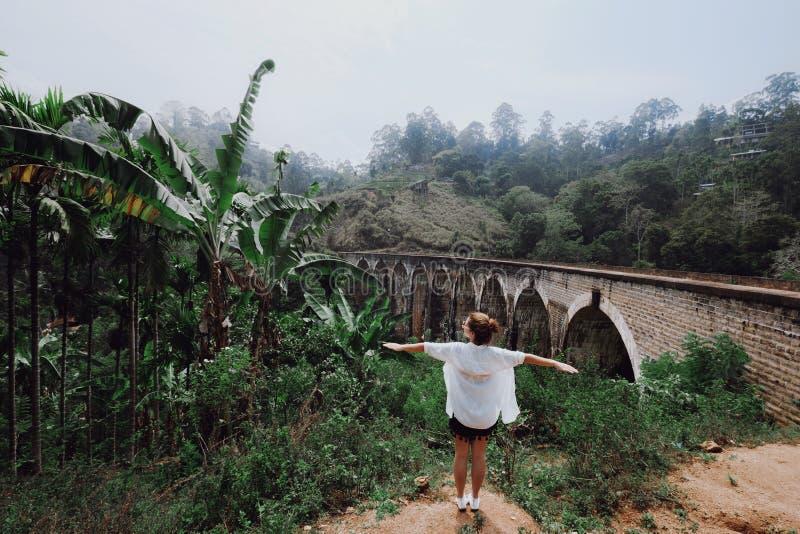 A menina com braços abre suportes contra a ponte foto de stock royalty free