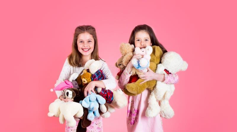 Menina com brinquedo As meninas guardam o montão de ursos de peluche Menina que abraça teddybears, infância Duas meninas felizes  fotos de stock