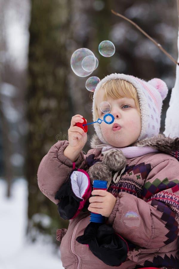 Menina com bubles do sabão no inverno imagem de stock