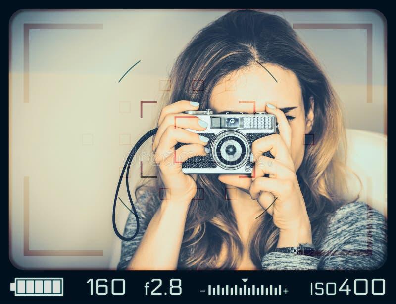 Menina com a câmera do vintage vista através do visor foto de stock