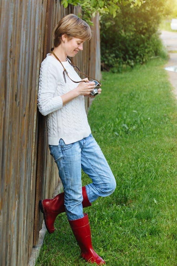 Menina com a câmera retro da foto perto da cerca fora foto de stock royalty free