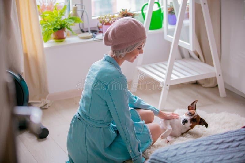 Menina com cão em casa fotografia de stock royalty free