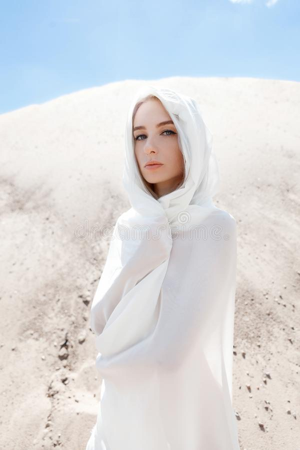 A menina com cabelo branco entre as montanhas da areia imagens de stock