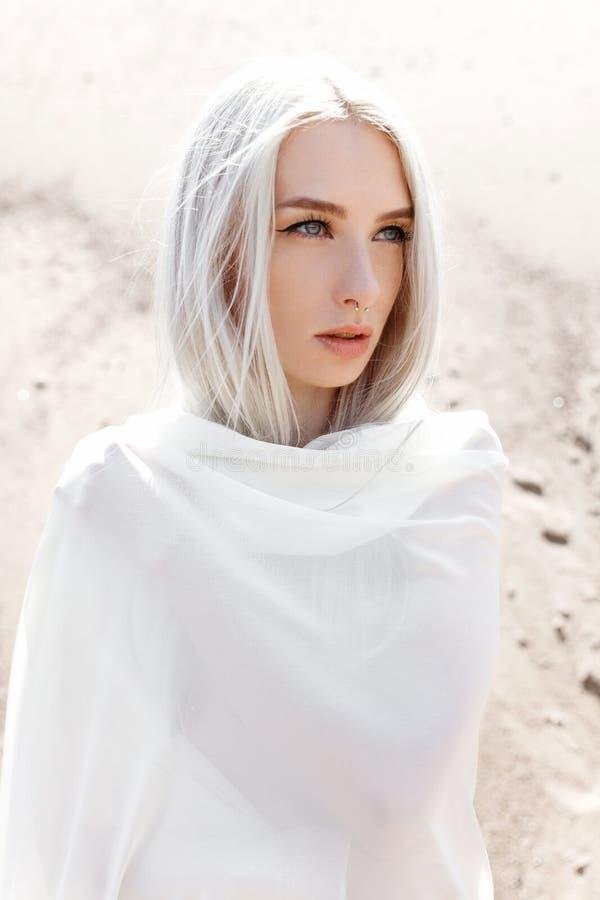 A menina com cabelo branco entre as montanhas da areia foto de stock royalty free