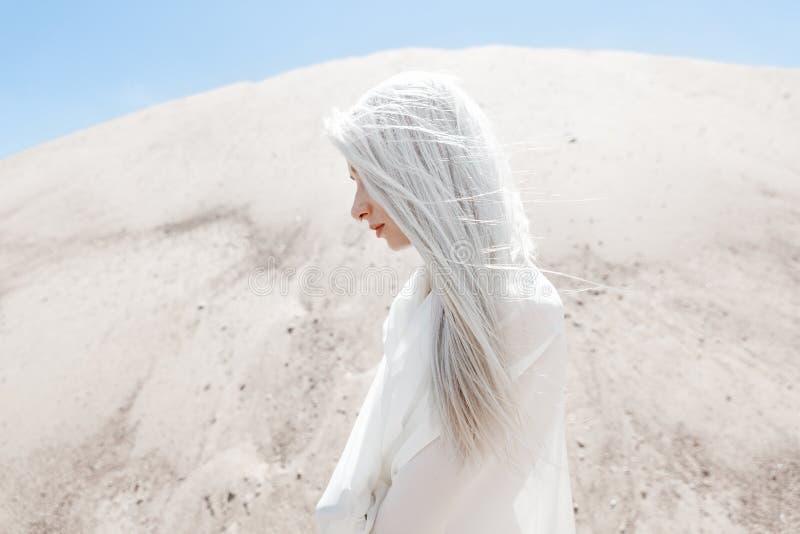 A menina com cabelo branco entre as montanhas da areia imagens de stock royalty free