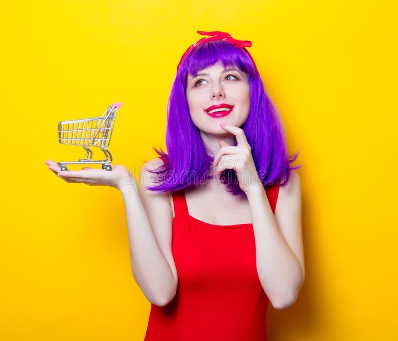 Menina com cabelo da cor e o carro roxos do supermercado fotografia de stock