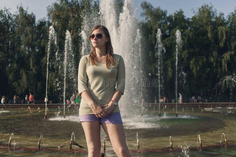 A menina com cabelo de fluxo no short curto e nos ?culos de sol est? estando na fonte fotografia de stock