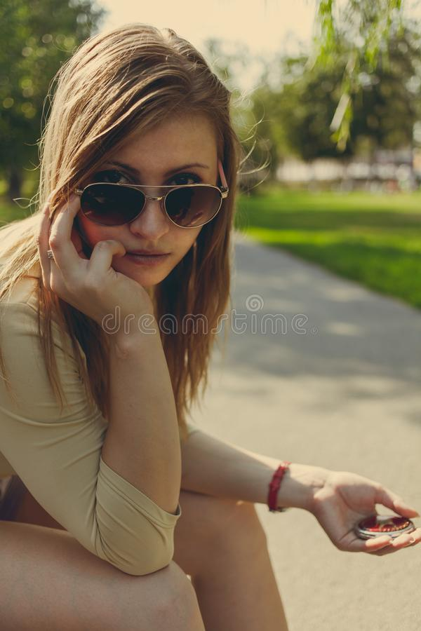 A menina com cabelo de fluxo nos óculos de sol olha no quadro sobre os vidros imagens de stock