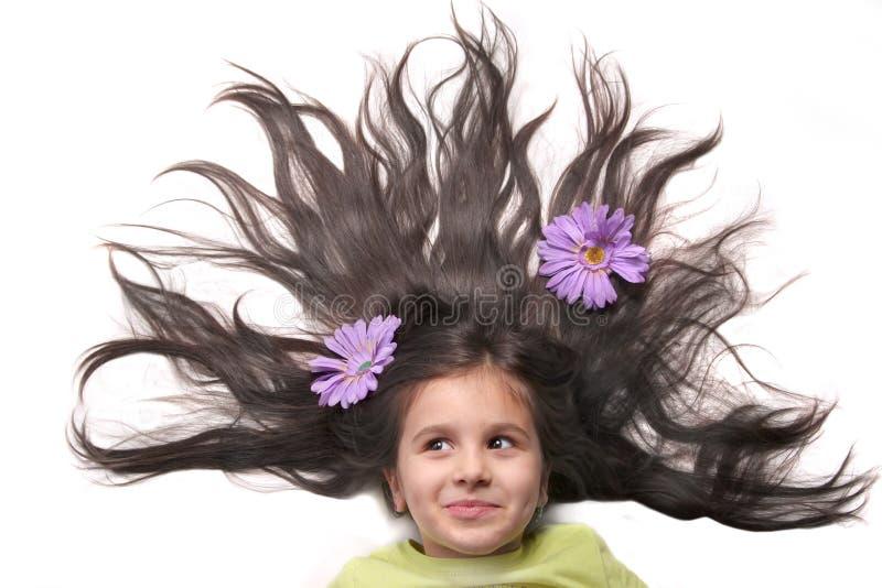 Menina com cabelo e as flores ventilados foto de stock