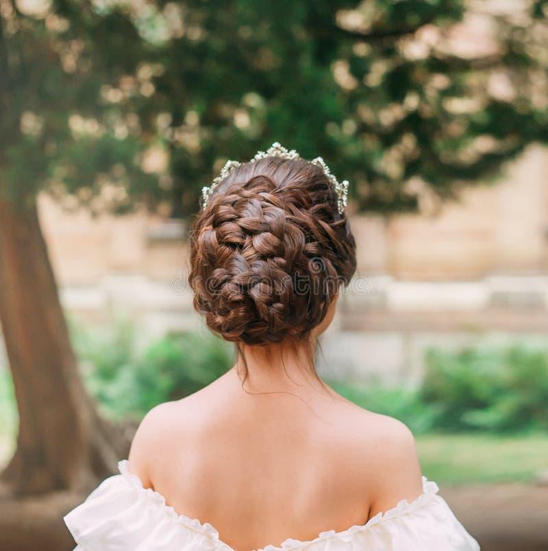 A menina com cabelo escuro e pele delicada mostra o penteado lindo do grande número de tranças, senhora está com ela de volta a fotografia de stock
