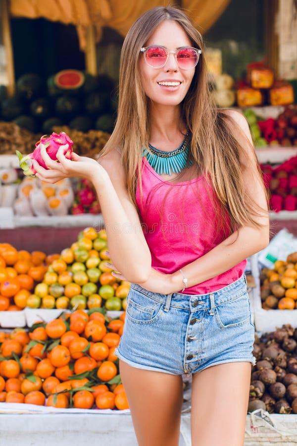 Menina com cabelo longo e bom corpo no fundo ropical dos frutos Veste óculos de sol cor-de-rosa, guarda o passionfruit e imagem de stock royalty free